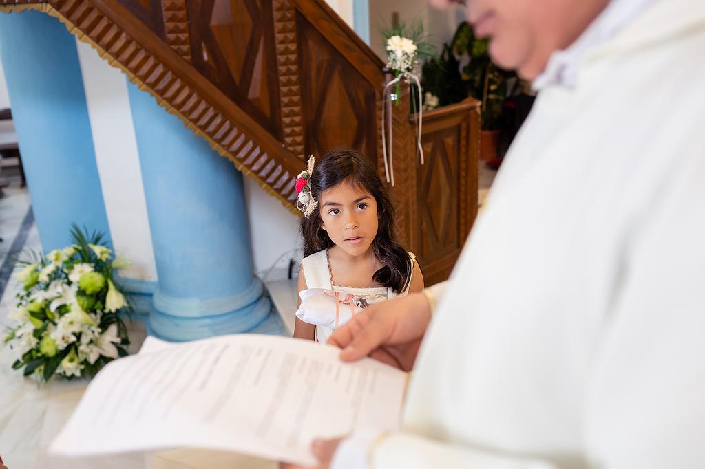 Niña con las arras mirando al sacerdote.
