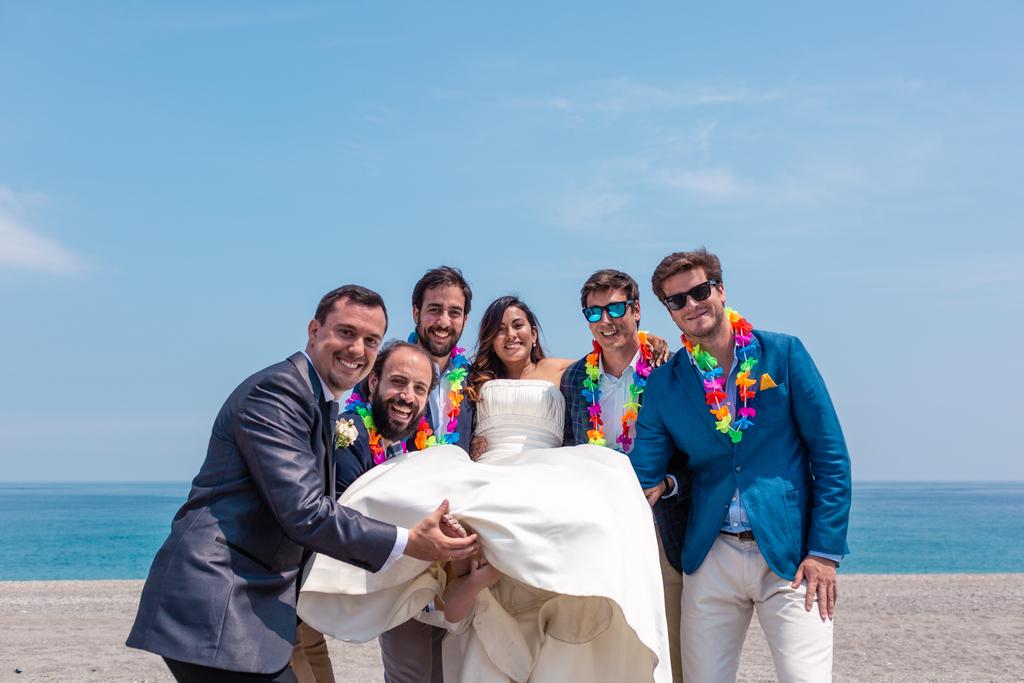 Amigos de los novios con la novia en brazos.