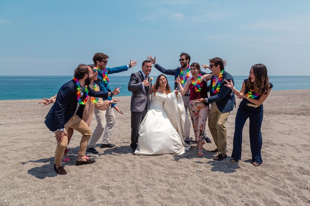 Novios y amigos bailando en la arena de la playa.