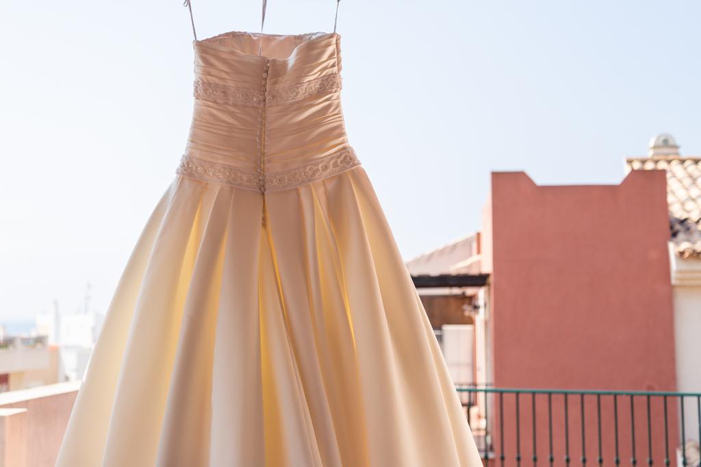 Vestido de novia colgado en una terraza al lado del mar.