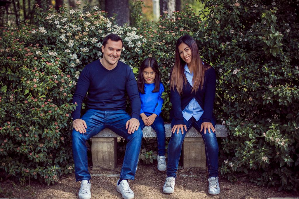 Pareja con su hija sentados en un banco de piedra.