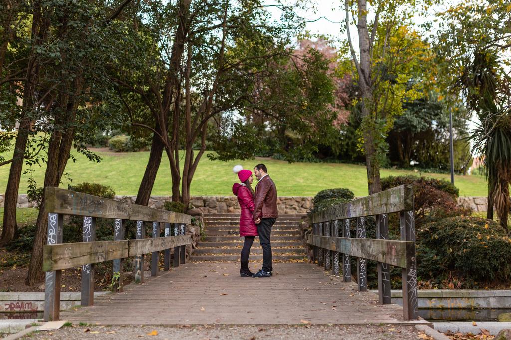 Pareja besándose encima de un puente.
