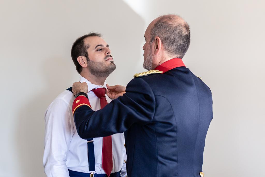 Padre del novio ayudándole a ponerse la corbata.