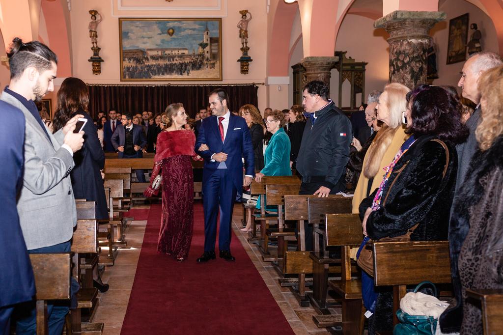 Novio entrando en la iglesia con su madre y madrina.