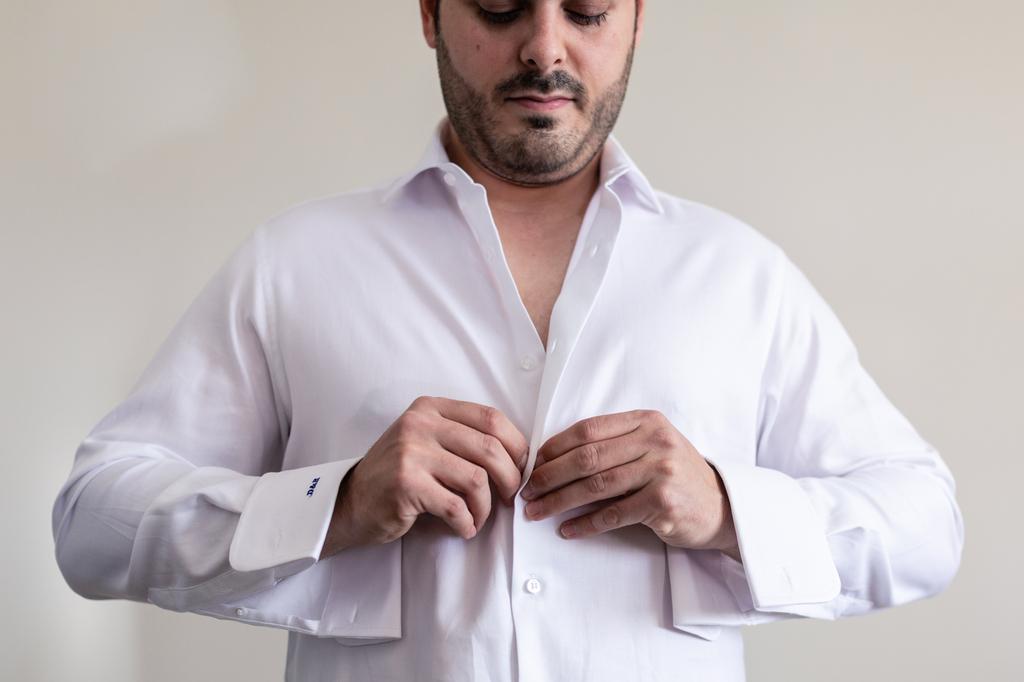 Novio abrochándose los botones de la camisa.